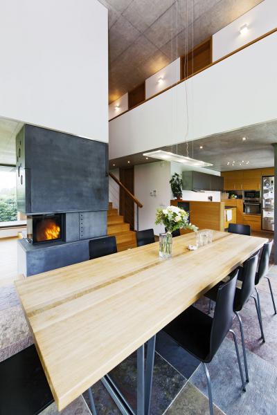 Srdcem domu je jídelna s tři metry dlouhým, na zakázku vyrobeným jídelním stolem. Vysoký strop a zdroje světla ze všech stran tu vytvářejí zvláštní atmosféru připomínající monumentální chrám. Otevřené vnitřní propojení mezi jednotlivými prostory jak v horizontálním směru, tak nahoru na galerii budí dojem rozlehlého domu