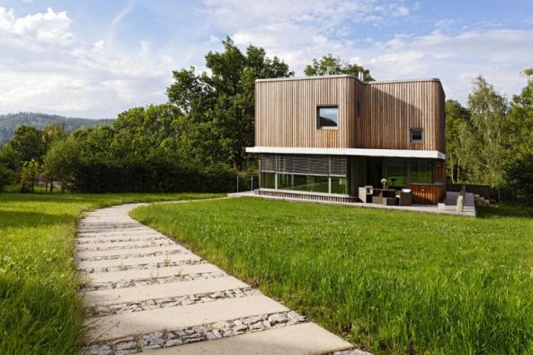 Architektonický koncept domu využívá kontrast lehkého, bohatě proskleného přízemí a kompaktního horního podlaží s modřínovým obkladem a několika menšími komponovanými okny
