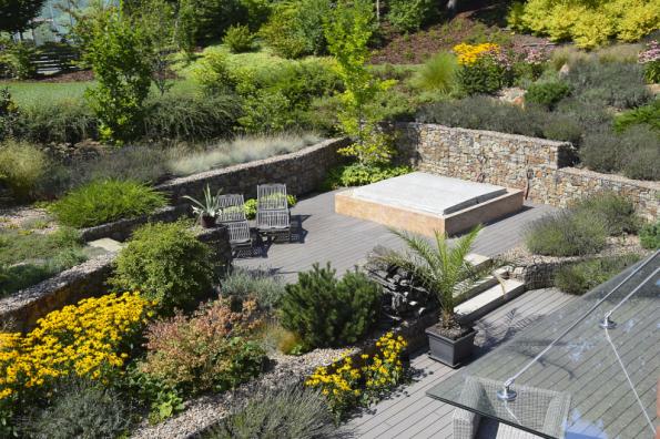 V soukromé zóně u domu se terénní převýšení vyřešilo pomocí systému gabionů. Na jednotlivých terasách pak byly založeny výsadby vyžadující přímé slunce. O toulavý stín se časem postarají solitérní stromy
