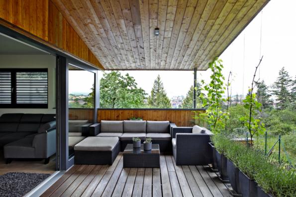 Z terasy na západní straně majitelé domu přehlédnou celé město, díky převýšení a okolní zeleni tu ale mají naprosté soukromí, od sousedů sem není vidět. Terasa poskytuje dostatečně velkou plochu pro pohodlné sezení či stolování. Se společnou obývací částí domu je propojena prosklenou posuvnou stěnou, přechod z interiéru do exteriéru je řešen jako bezbariérový. Ochranu před deštěm a prudkým sluncem zajišťuje přesah střech y s rohovým ocelovým sloupkem. Podlahu tvoří odvětrávaná dřevěná paluba s odvodňovacím systémem