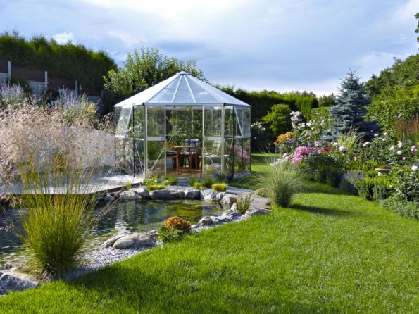 """Díky velkým proskleným plochám se skleník v zahradě částečně """"ztrácí"""" a nepůsobí tak mohutným dojmem"""