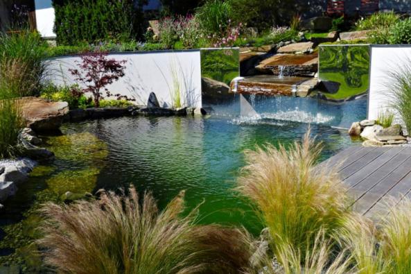 Opěrná zídka je přerušena vodopádem v nezvyklé kombinaci materiálů. V popředí vidíme vysoce dekorativní trávu kavyl péřovitý