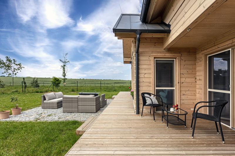 Pozemek na kraji obce nabízí krásný výhled do okolí. Z obývacího pokoje se dá skleněnými dveřmi vyjít na terasu vybavenou sezením v přírodním stylu