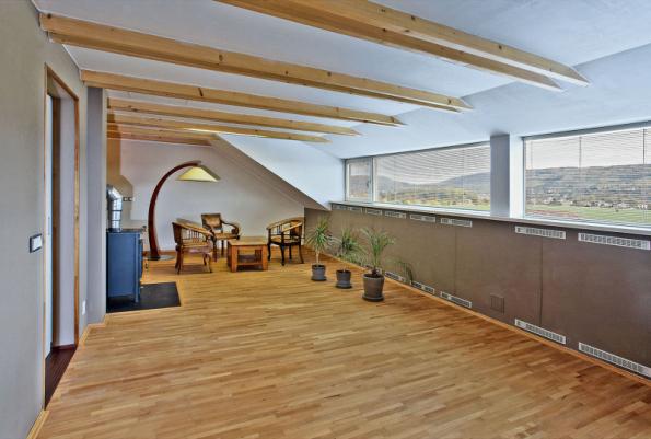 Místnost v podkroví, která byla vybudována dodatečně během stavby, vděčí za svůj vznik panoramatickému výhledu zobrazujícímu se v pásovém okně. V parapetu je integrováno vytápění