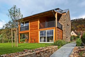 Dřevěná okna a prosklené plochy zvýrazňují rámy se světlým nátěrem