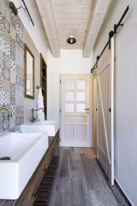 K ložnici majitelů patří vlastní koupelna s dvojumyvadlem a přilehlým WC. Působivý autentický výraz vytvářejí dřevěné a kovářské prvky v kombinaci s trámovými stropy