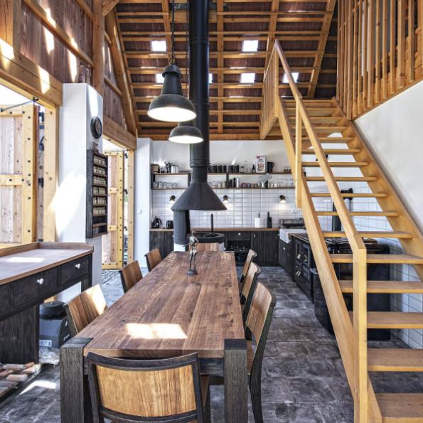 Černá kuchyň ve stodole podle návrhu architektů. Dominantou je otevřený pohled do krovu, otevřené ohniště a kuchyňská linka s masivním dřevěným stolem pro 8 osob