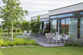 Dům je všemi ložnicemi otevřený do zahrady, architekti se pokusili zeleň přitáhnout co nejblíže oknům. Druhovým složením jde o přírodní zahradu, tady však má velmi moderní design