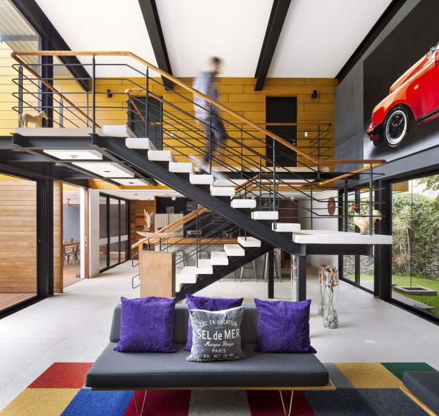 Stropní vazníky a konstrukce schodiště z válcovaných ocelových profilů, které jsou ještě zvýrazněné černým nátěrem, dávají společné obývací části domu jednoznačný industriální ráz. Ložnicová část je odlišena dřevěným obložením stěn