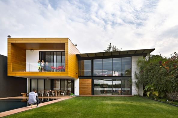 Kombinace industriálního a přírodního stylu se promítá i do fasády domu: prosklené plochy a přiznané ocelové nosníky sousedí s dřevěným obkladem a hladkou bílou omítkou. Pultová střecha s atypickým podélným sklonem příjemně osvěžuje přesnou geometrickou kompozici a vybočuje z pravoúhlého stereotypu