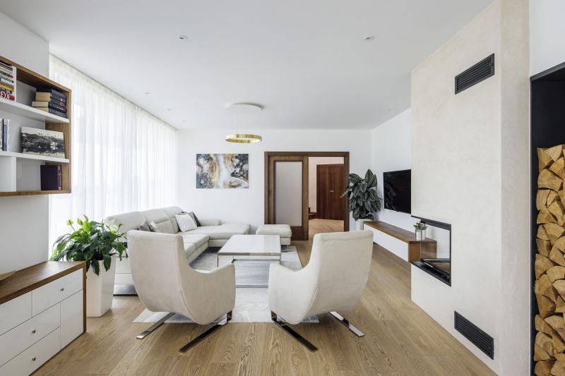 Z haly se posuvnými dveřmi vstupuje do společné obývací části. Jednotícím prvkem interiéru celého domu je přírodní dubové dřevo, bílá barva a základní geometrické tvary. Pojetí je záměrně jednoduché a nekontrastní, aby vždy zůstaly dominantní výhledy do krajiny
