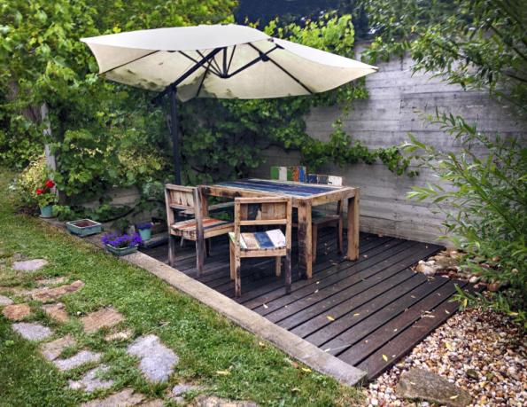 """Posezení s vintage námořnickým nábytkem odděluje od sousedů stěna z litého betonu. Prkna byla před """"šalováním"""" důkladně okartáčována, aby se pak struktura dřeva pěkně otiskla do betonu"""