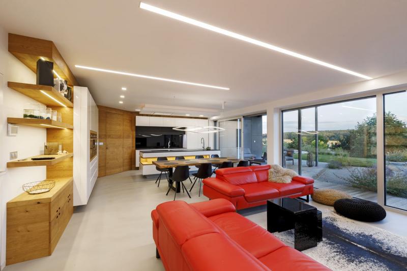 Přehlednému interiéru dominuje červená sedací souprava a zajímavě řešené osvětlení v podhledu. Dodavatelem vybavení interiérů bylo Truhlářství Fencl
