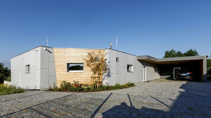 Dům je postavený z cihel HELUZ, zateplený a má zavěšenou fasádu z desek dvou barev. Je situován k severní hranici pozemku a z této strany je maximálně uzavřený