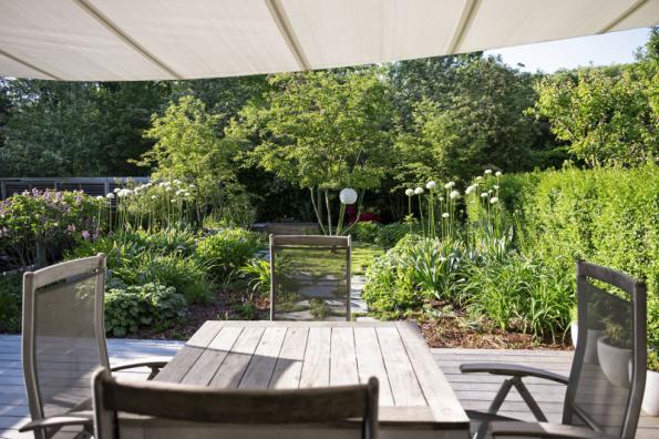 Terasa v návaznosti na obývací pokoj představuje otevřený prostor slunného charakteru. Opakující se vícekmenné dřeviny dodávají prostoru dynamiku. Prostor zahrady je maličký, ze tří stran intenzivně napojený na sousedy. Je to vlastně takové protažení obýváku do exteriéru