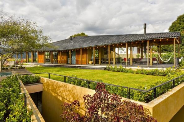 Dřevěný bungalov má funkci společného obývacího prostoru a je propojen schodištěm se spodním zděným ložnicovým podlažím (na fotografii vpravo dole). Na střeše ložnic architekti vytvořili vyhlídkovou terasu s lehátky a květinami
