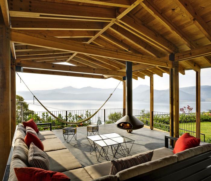 Krytá terasa na východní straně nad jezerem je vybavena jako letní obývací pokoj, včetně zavěšeného ocelového krbu a stolu pro venkovní stolování