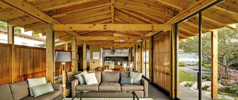 Uprostřed společného obývacího prostoru se nachází blok s kuchyní, zázemím a schodištěm, který rozděluje bungalov na dvě části: uzavřenou a otevřenou. Jídelnu s obývacím pokojem lze po obvodě uzavřít (či otevřít) posuvnými prosklenými stěnami a dřevěnými panely, které slouží k zastínění. Na opačné straně se nachází zastřešená obytná terasa. Kamenná dlažba bezbariérově přechází do zahrady a rostliny a skály působí dojmem, že vstupují do interiéru. Podařilo se tak dosáhnout maximálního propojení domu s přírodou
