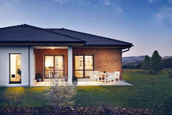 Nenápadný nízký dům s valbovou střechou se propojuje se zahradou přes rohovou terasu, kterou zútulňuje cihelný obklad. Dá se tu relaxovat na sluníčku i posedět v příjemném stínu u jídelního stolu