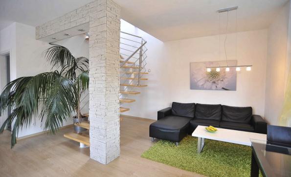 Ocelodřevěné schodiště je přímou součástí obývacího pokoje. Velmi se tím šetří místo, vzdušná konstrukce také prosvětluje prostor
