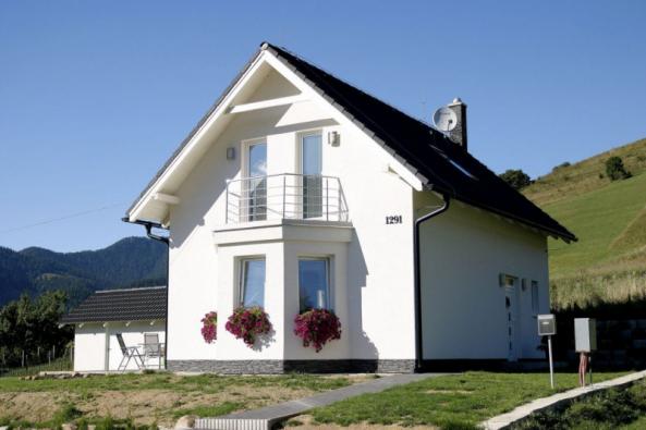 Dům má klasický tvar se sedlovou střechou a symetrické hlavní průčelí s balkonem (typ Ekonomik N7, dispozice: 4 + kk, užitková plocha: 98 m2)