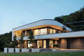 Architektonickým cílem bylo, aby budova harmonicky splynula se svažitým pozemkem a současně vznikl akcent v rámci okolí (foto: Jochen Helle/Schüco)